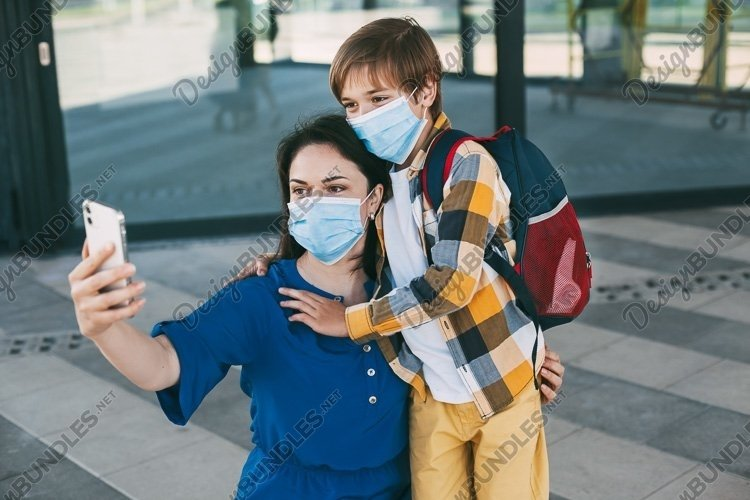 Mom and child with a backpack wearing a mask take a selfie example image 1
