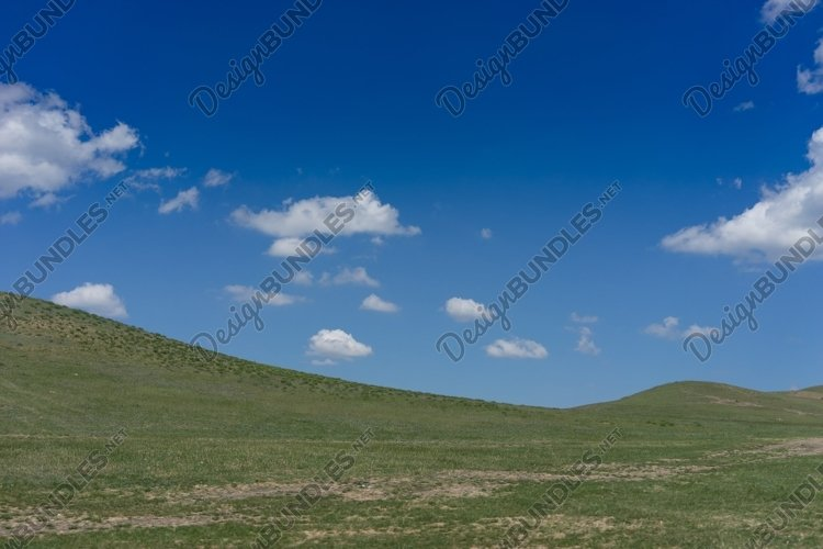 Natural landscape with hills against blue sky with white clo example image 1