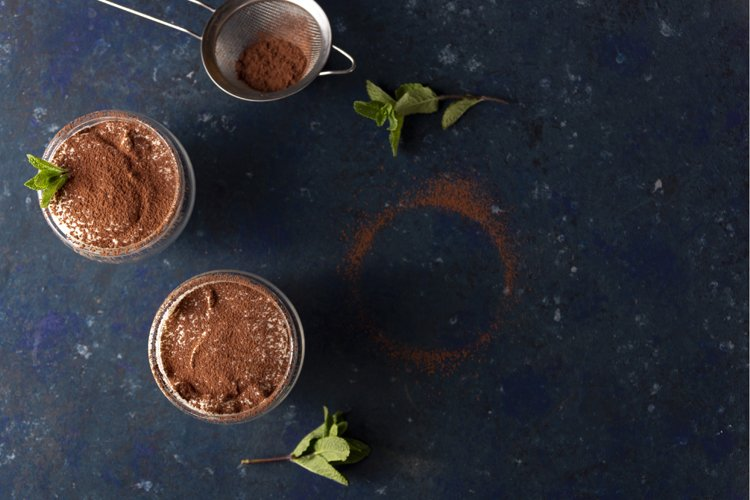 Two servings of tiramisu garnished with cocoa and mint example image 1