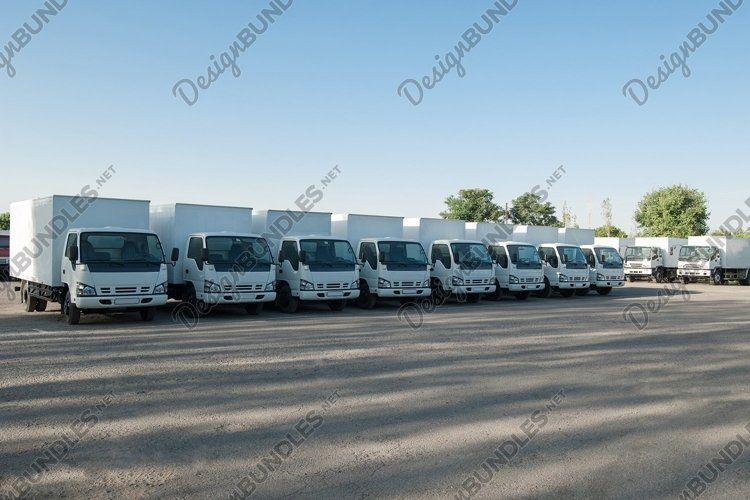 Cargo vehicles stand in a row on a parking. Truck park example image 1