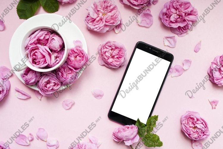 Mobile phone, pink flowers pink background. Place for text. example image 1