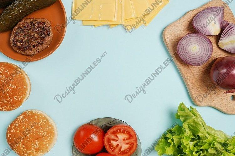 Hamburger ingredients on blue table background, food frame