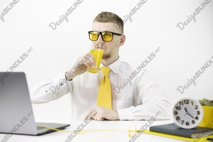 Handsome male office worker drinks orange juice example image 1