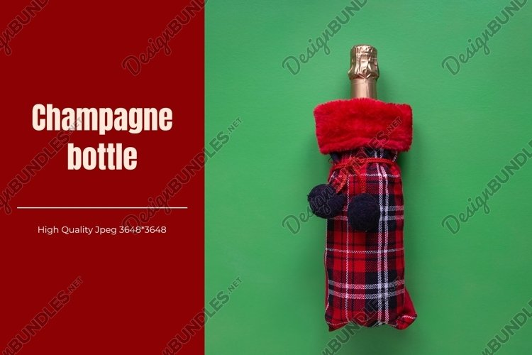Champagne bottle in checkered bag on green background