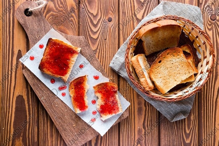 sandwich of toast and jam drops on a cutting board example image 1