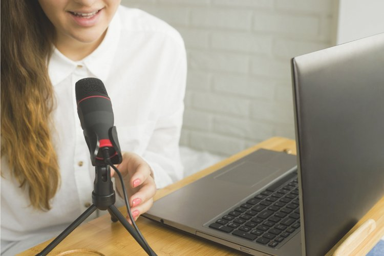 A blogger records a podcast into a microphone at home. example image 1