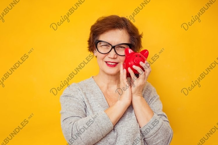 Elderly positive woman holds piggy bank on yellow background example image 1