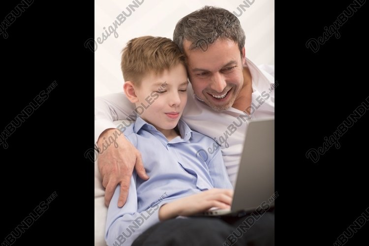 Happy dad and son with laptop at home example image 1