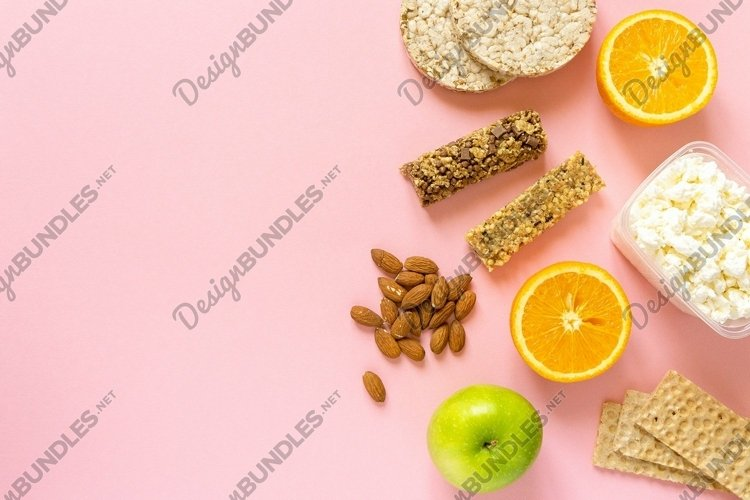 Flat lay of healthy snacks on pink background