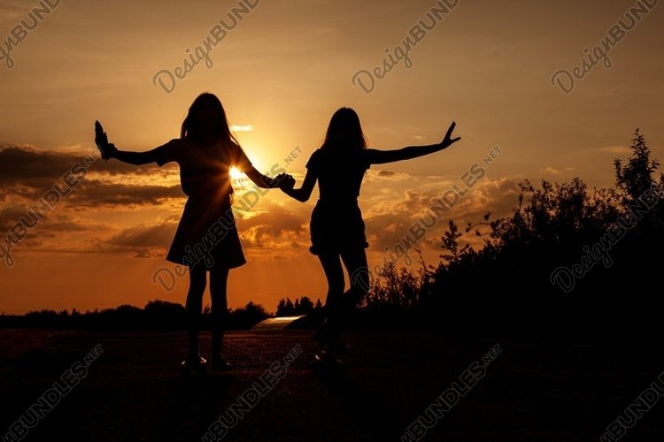 Two blond teenage girls ride skateboards at beautiful sunset example image 1