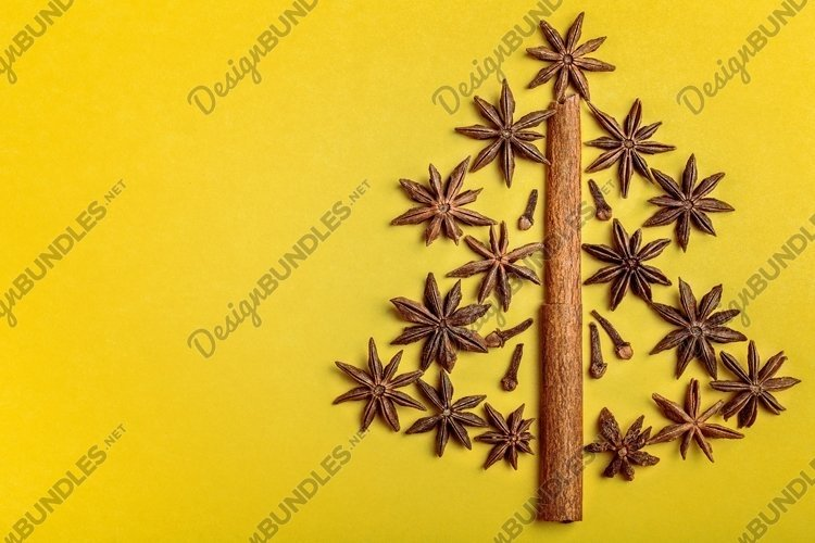 Christmas tree made with brown spices on yellow paper. example image 1