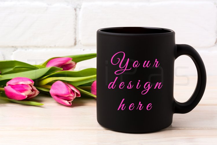 Black coffee mug mockup with rich magenta pink tulips bouquet near painted brick wall.