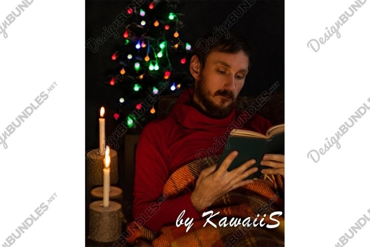 Man reads book at home burning candle glowing Christmas tree example image 1