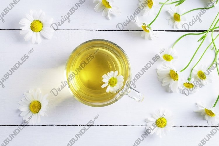 Close-up top view of a cup of chamomile tea and flowers