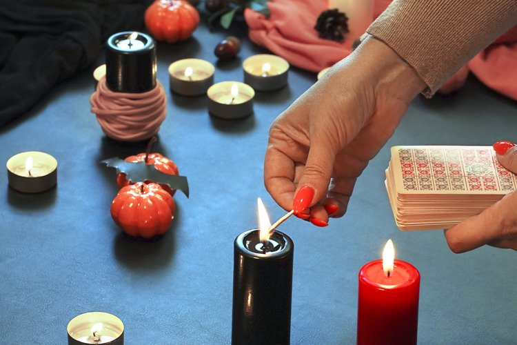Blurred hand with matchstick, lighting a Candle. Halloween example image 1