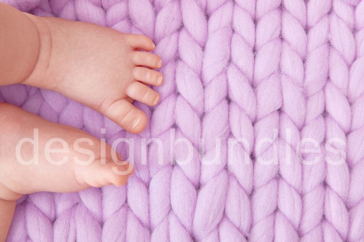 Cute baby feet on a large knitted lilac plaid. Greeting card example image 1