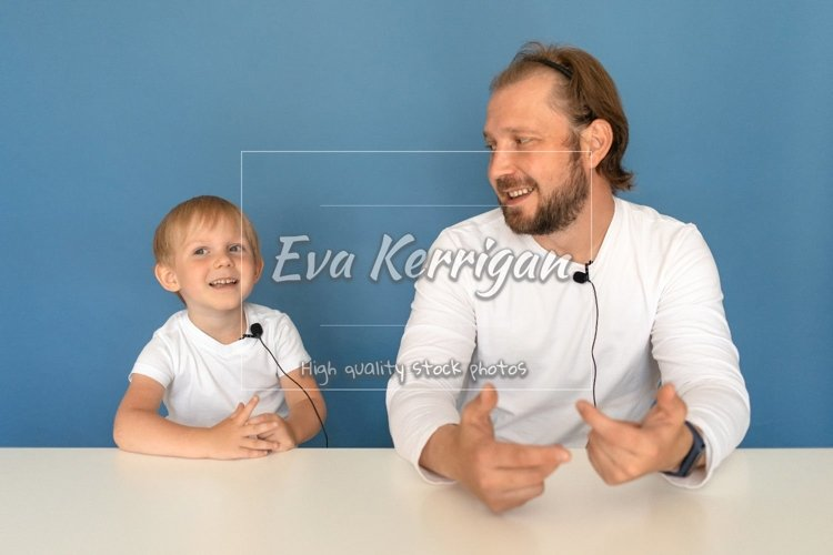 Two people, father and son, a man and child blogger. example image 1