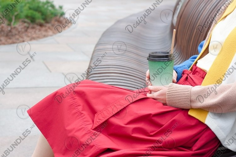 A woman holds a takeaway coffee in a paper cup in a park.