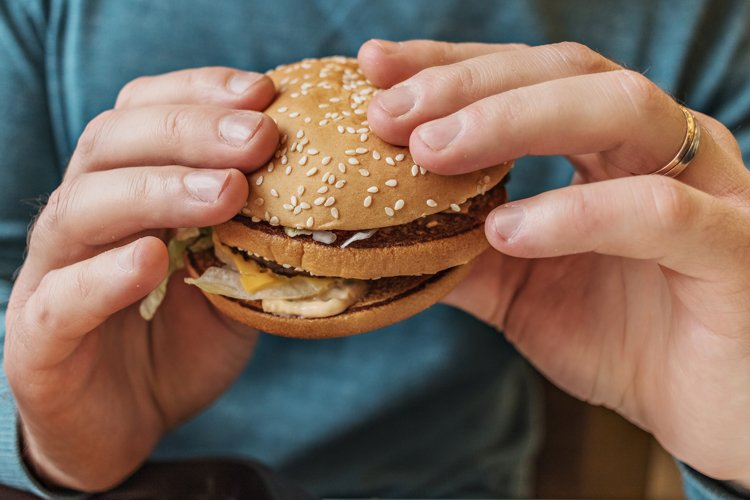 Men's hands hold a fresh tasty burger. example image 1