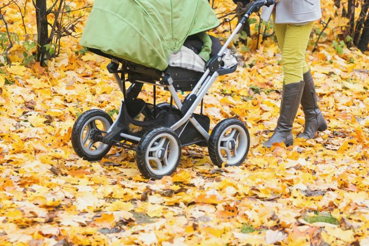 Mother strolling a pushchair with a sleeping baby
