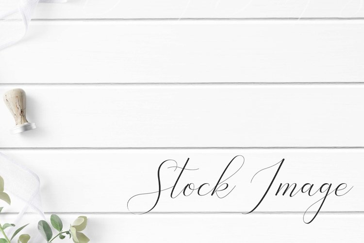 Styled Stock with greenery and white ribbon on white wood.