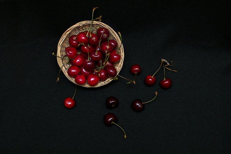Cherry in a wicker basket on a black background example image 1
