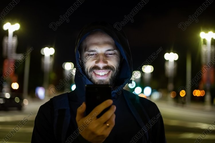 smiling man in the night city looks at the phone example image 1