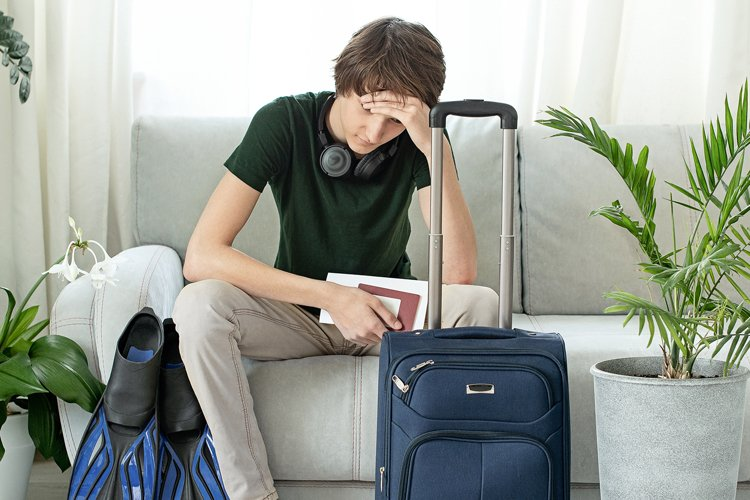 Sad tourist teen with a suitcase and flippers stays at home