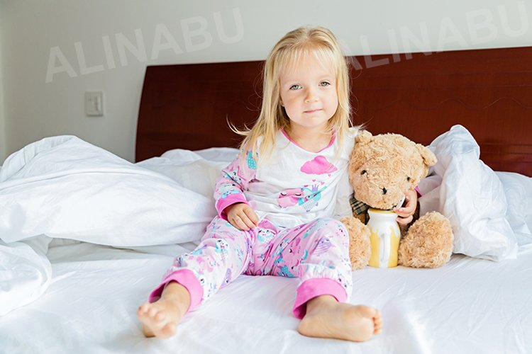 Little girl with teddy bear sitting on the bed example image 1