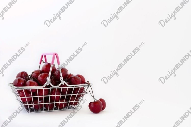 Shopping basket full of sweet berries on white background. example image 1