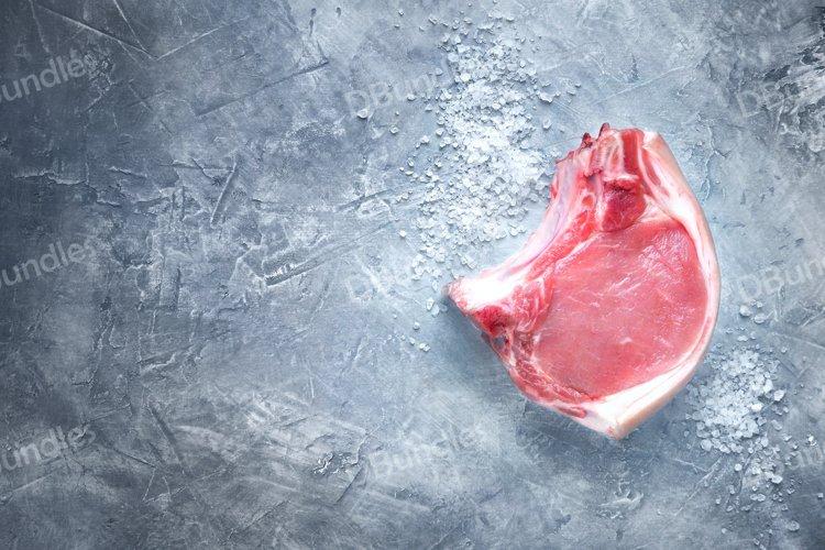 Raw meat pork steak with salt on a dark background