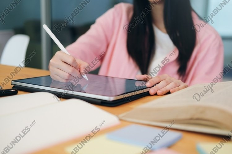 Young collage student using computer and mobile device. example image 1