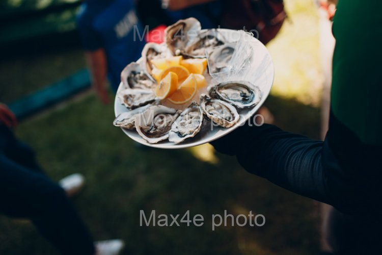 The waiter serves oysters with lemons on a platter. Catering