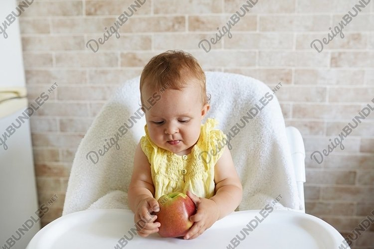 Adorable baby holding apple on table of feeding chair example image 1