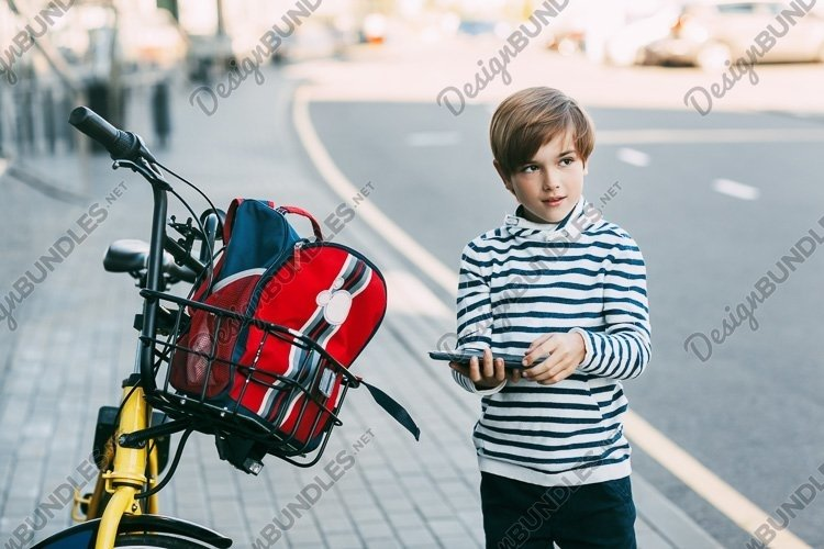 Schoolboy with tablet and backpack on a bicycle example image 1