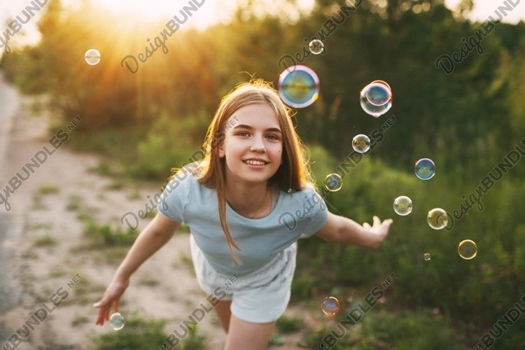 Cute girl catches soap bubbles on a sunset background. example image 1
