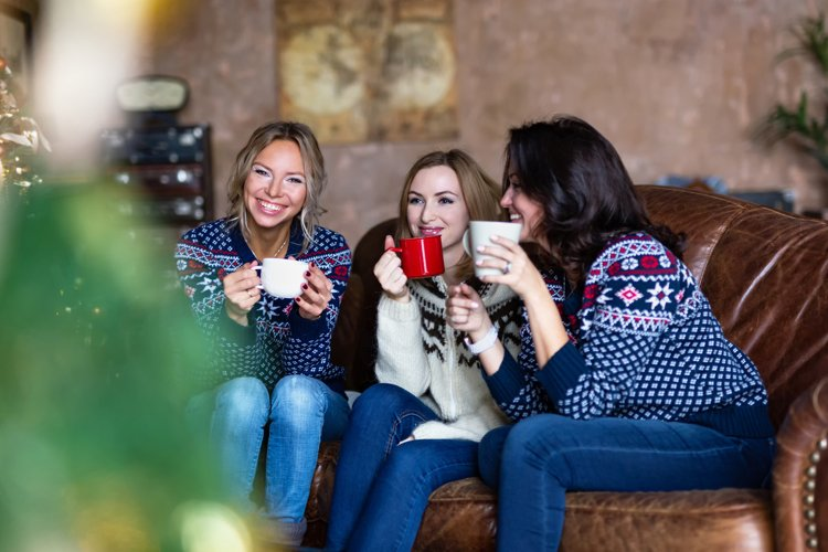Three smiling women talking and drinking coffee