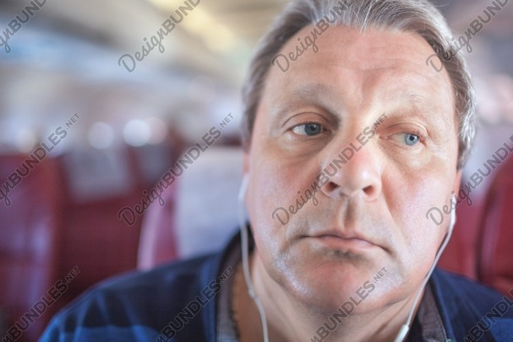Man listening to music in the airplane example image 1