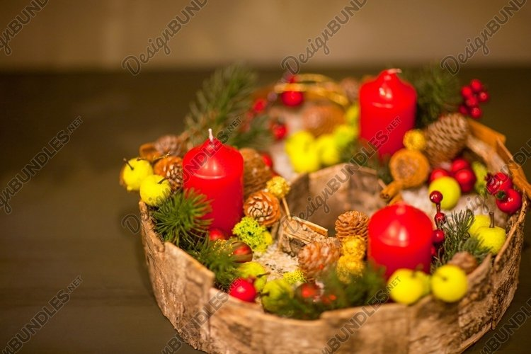 Red Christmas candle in a basket with berries and fir cones example image 1