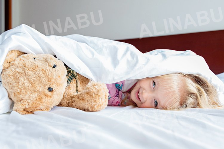 Little girl with teddy bear lying on the bed example image 1