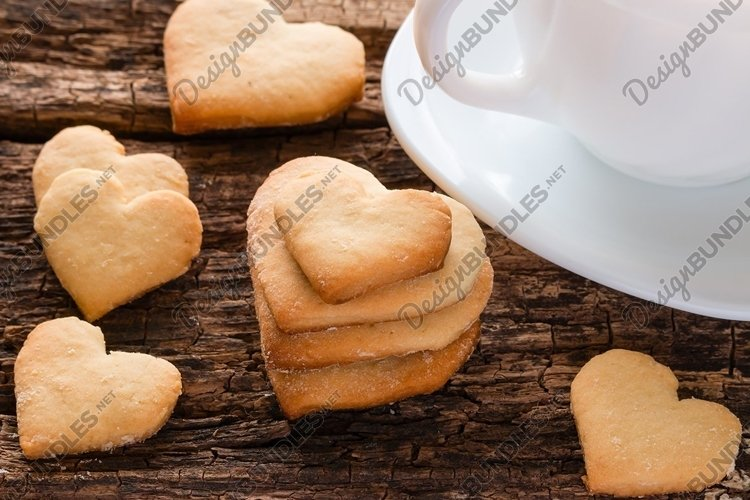 homemade cookies in the shape of heart and white cup