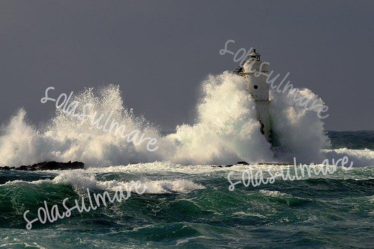 Waves smash against lighthouse.