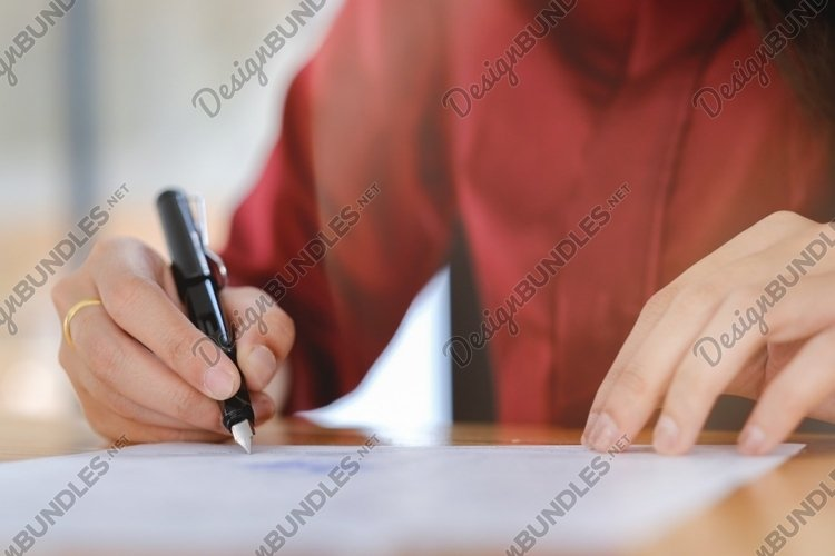 Businesswoman signing a contract document making a deal. example image 1