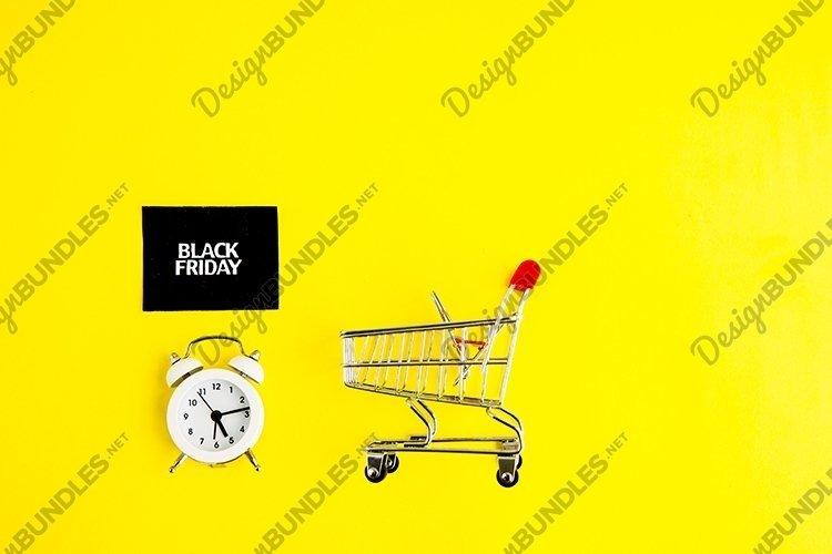White alarm clock, a shopping cart, black Friday