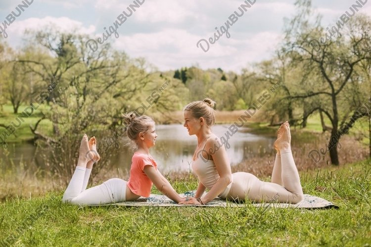 Young mom with her daughter doing yoga outdoors in the park. example image 1