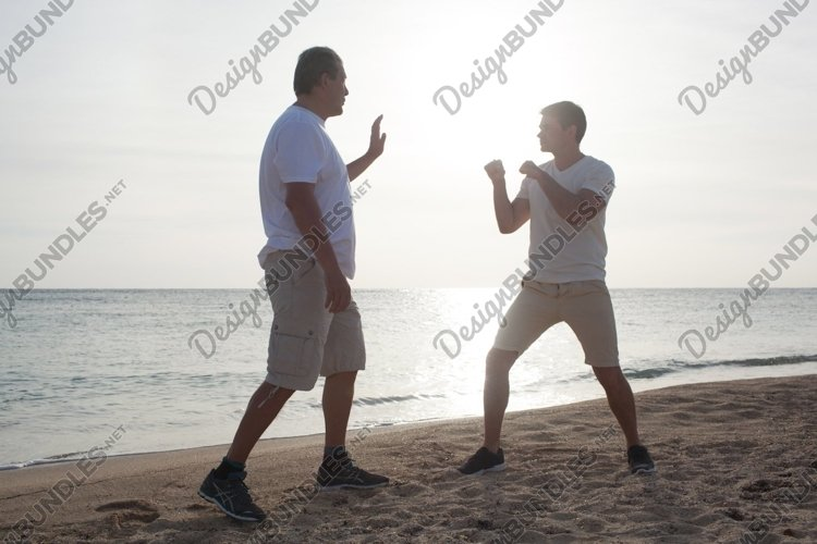 Two men having boxing training on the beach example image 1