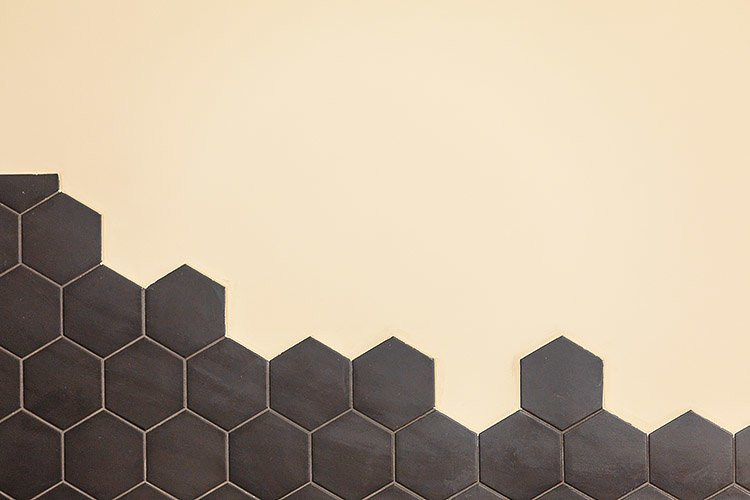 Hexagonal black tile on a light wall. Copy space. example image 1