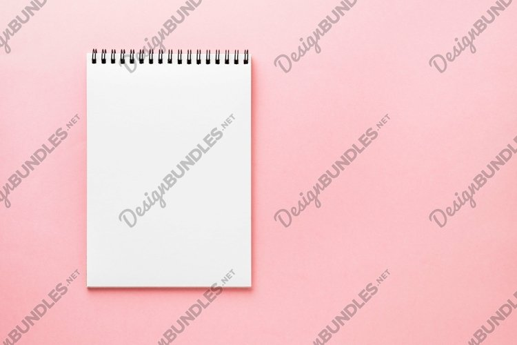 Blank notepad white page on pink desk, color background. Top