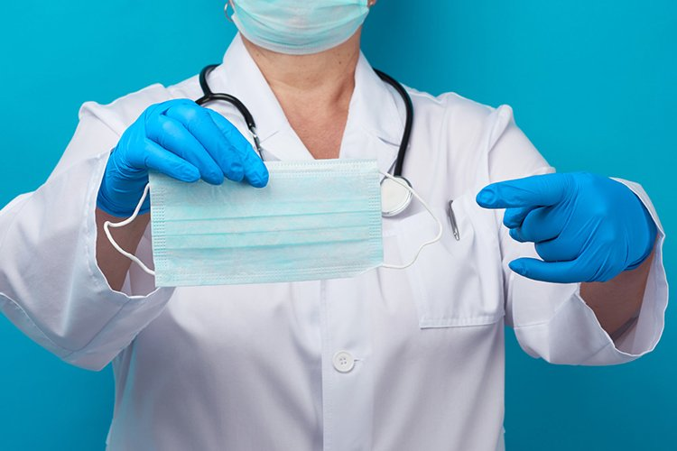 doctor in a white coat and mask holds a stack masks example image 1