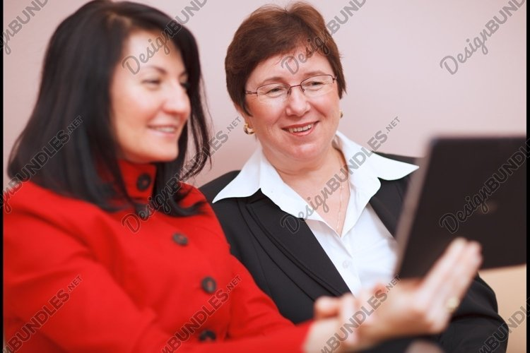 Two women sharing a tablet computer example image 1